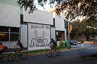 """Bike Riders ride past the famous """"Hi, How Are You"""" Mural, a famous tourist attraction on the UT Drag"""