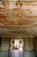 The wood ceiling of this salon has a faded mural depicting two ladies riding in a chariot