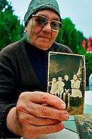 Bucarest / Romania 2007.Porraimos, una delle pagine meno note della storia dei Rom, l'Olocausto degli zingari. Il regime filo-nazista di Antonescu, durante la seconda guerra mondiale deportò migliaia di Rom nei campi di sterminio al confine tra Polonia e Ukraina..Nella foto Branzan Anuta, nata nel 1934 e unica sopravvissuta al genocidio della sua famiglia. Deportata con le sorelle e i genitori dalle milizie rumene nei campi di concentramento della Transnistria. Durante l'intervista mostra le foto dei famigliari uccisi: la madre Costantina e il padre Radu, le sorelle Virginica, Margherita e Marieta. Nella foto, la piccola Anuta indossa l'abito nero..Foto Livio Senigalliesi..Bucarest / Romania 2007.Porraimos, one of the lesser-known pages of the history of the Roma, the Holocaust of the Gypsies. The Antonescu's pro-Nazi regime during the Second World War, deported thousands of Roma to extermination camps on the border between Poland and Ukraine..In the photo Mrs.Branzan Anuta, born in 1934, the only survivor of the genocide of his family. Deported with her sisters and parents by the pro-Nazi militias to the concentration camps in Transnistria. During the interview shows photos of family members killed: the mother Constantine, the father Radu, sisters Virginica, Margaret and Marieta. .In the picture, Anuta is wearing the black dress..Photo Livio Senigalliesi.