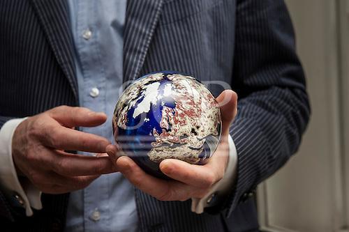 London, England. Businessman holding a globe of the Earth made of semi-precious stones.