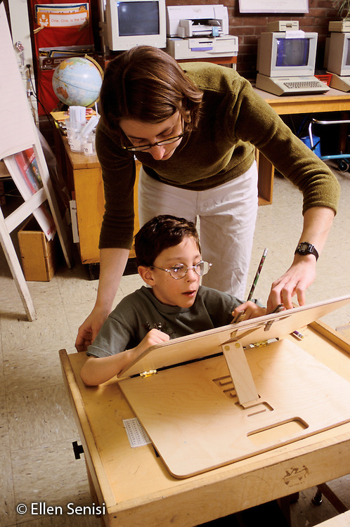 MR / Schenectady, NY.Zoller Public School - Inclusion Class - Grade 1.Special education teacher helps boy (7, cerebral palsy) with work at specially-designed desk..MR: Aba1.PN#: 28624                      FC#: 21600-00103.scan from slide.© Ellen B. Senisi