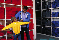 AFRICAN-AMERICAN FATHER AND SON IN STORE FITTING A SWEATSHIRT. AFRICAN-AMERICAN FATHER AND SON. OAKLAND CALIFORNIA.
