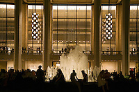 People gathered around the fountain in the main COURTYARD of LINCOLN CENTER at night - NEW YORK CITY