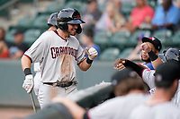 Left fielder Kole Enright (12) of the Hickory Crawdads is greeted after scoring a run in a game against the Greenville Drive on Friday, June 18, 2021, at Fluor Field at the West End in Greenville, South Carolina. (Tom Priddy/Four Seam Images)