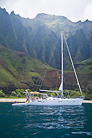 Young man and woman on a cruising sailboat off of Kalalau Beach on the Na Pali Coast of Kauai