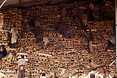 Burundi; workers, many of them teenagers, stacking timber in a shed.