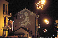 """Switzerland. Canton Tessin. Vira Gambarogno. Video projection on the wall of mary holding in her arms Jesus. Mary, called since medieval times Madonna (My Lady), is known from the New Testament as the mother of Jesus of Nazareth. The New Testament describes her as a young maiden who conceived by the agency of the Holy Spirit whilst she was already the betrothed wife of Joseph of the House of David and awaiting their imminent formal """"Home-taking"""" ceremony (the concluding Jewish wedding rite). To many believers the accounts in the canonical """"Birth narratives"""" suggest that she had still been a virgin at the time of the child's birth as well as at his conception. Illuminaion at night for the Christmas holiday season. Stars. © 2007 Didier Ruef"""