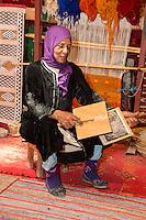 Morocco.  Amazigh Berber Woman Carding Wool, Ait Benhaddou Ksar, a World Heritage Site.