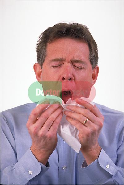 man sneezing into tissue