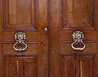 Detail of an oak double door with brass knockers