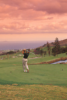 Man playing golf at sunset