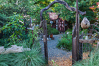 View into the Hermit's garden through a rustic gateway and Muhlenberia lindhiemeri grasses; Kate Frey Garden
