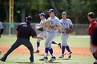 New York University Violets first baseman Colman Hendershot (34) is thrown out by the field umpire for a hard tag as Trevor Francesconi (7) looks on during a game against the Edgewood Eagles on March 14, 2017 at Terry Park in Fort Myers, Florida.  NYU defeated Edgewood 12-7.  (Mike Janes/Four Seam Images)