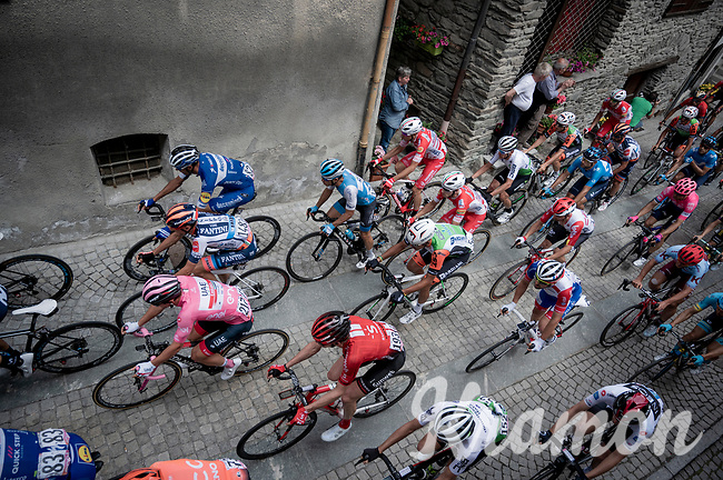 peloton with the Maglia Rosa / overall leader, Jan Polanc (SVK/UAE-Emirates) rolling through town<br /> <br /> Stage 14: Saint Vincent to Courmayeur/Skyway Monte Bianco (131km)<br /> 102nd Giro d'Italia 2019<br /> <br /> ©kramon