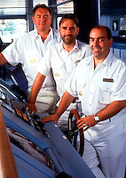 Crewmen behind the wheel of cruise ship