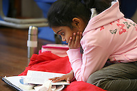 "Reading a book during a break.  Drama group for 8-13s run by Yvonne Arnaud Theatre, rehearsing a production of ""Alice"" in a school hall, Guildford, Surrey."