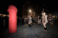 Pictured: Men and women in ancient Greek outfits parade through the streets with a giant phallus in Athens, Greece.<br /> Re: The ancient tradition of the Phallic procession, or Penis Parade, which was part of Dionysiac celebrations in ancient Greece, has taken place in central Athens. The processions were characterized by obscenities and verbal abuse and the display of a fetishized phallus was a common feature.