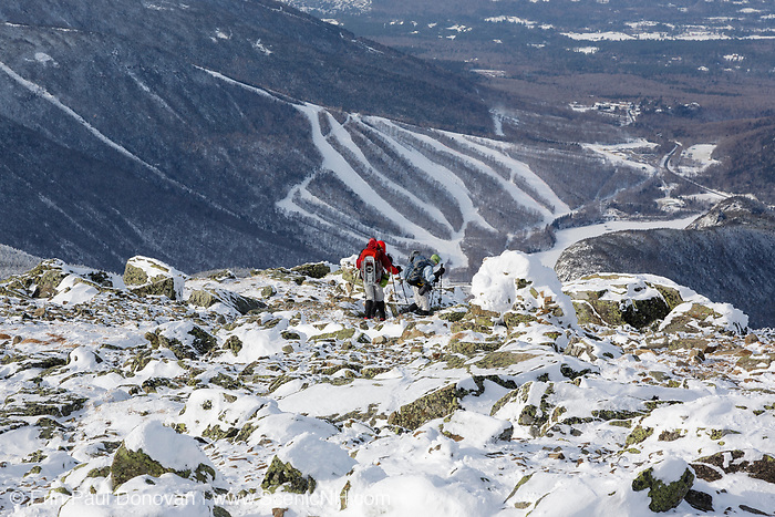 Three hikers descending the Greenleaf Trail from the summit of Mount Lafayette in the New Hampshire White Mountains. Cannon Mountain ski area can be seen in the background. The Appalachian Trail travels over the summit of Mount Lafayette.