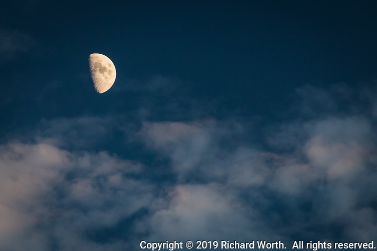 A barely gibbous moon with clouds against a blue sky from an urban backyard in the San Francisco Bay area, October 2019.