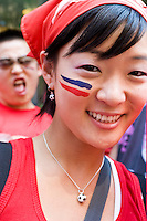 """South Korea fan Shin Park shows off her colors while watching her team play against France on June 18, 2006 on a giant outdoor television in a section of New York City known as """"Korea Way"""".<br /> <br /> The World Cup, held every four years in different locales, is the world's pre-eminent sports tournament in the world's most popular sport, soccer (or football, as most of the world calls it).  Qualification for the World Cup is open to any country with a national team accredited by FIFA, world soccer's governing body. The first World Cup, organized by FIFA in response to the popularity of the first Olympic Games' soccer tournaments, was held in 1930 in Uruguay and was participated in by 13 nations.    <br /> <br /> As of 2010 there are 208 such teams.  The final field of the World Cup is narrowed down to 32 national teams in the three years preceding the tournament, with each region of the world allotted a specific number of spots.  <br /> <br /> The World Cup is the most widely regularly watched event in the world, with soccer teams being a source of national pride.  In most nations, the whole country is at a standstill when their team is playing in the tournament, everyone's eyes glued to their televisions or their ears to the radio, to see if their team will prevail.  While the United States in general is a conspicuous exception to the grip of World Cup fever there is one city that is a rather large exception to that rule.  In New York City, the most diverse city in a nation of immigrants, the melting pot that is America is on full display as fans of all nations gather in all possible venues to watch their teams and celebrate where they have come from."""