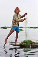 Myanmar, Burma.  Intha Fisherman Preparing his Net, Balancing on one Leg, in the Style Customary to Inle Lake, Shan State.