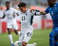 DENVER, CO - JUNE 19: Luis Paradela #23 tries to evade Jean-Sylvain Babin #6 during a game between Martinique and Cuba at Broncos Stadium on June 19, 2019 in Denver, Colorado.