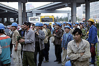 Construction workers wait for bus after finish working in Beijing, China..