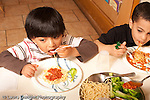 Preschool Headstart 3-5 year olds meal lunch time two boys eating spagetti and sauce vegetable broccoli. horizontal