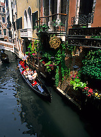Tourists on romantic gondola ride on canal with gondolier in picturesque Venice Ital