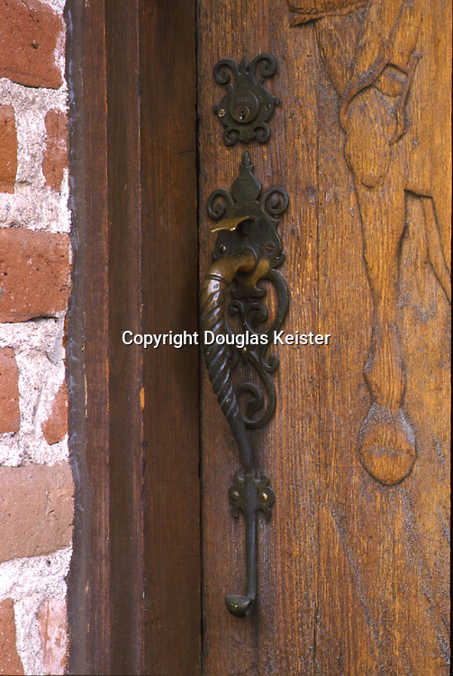 This superb forged lockset at the door of the Murphey Building Company sales office surely gave prospects a solid first impression; its delicately-wrought backplate is complemented by a matching escutcheon on the deadbolt.  The carved relief partially visible at right is that of a Pony Express rider on his rounds.