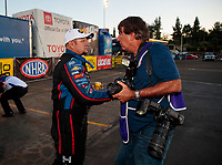 Nov 17, 2019; Pomona, CA, USA; NHRA funny car driver Robert Hight (left) is congratulated by photographer Ron Lewis as he celebrates after clinching the 2019 funny car world championship during the Auto Club Finals at Auto Club Raceway at Pomona. Mandatory Credit: Mark J. Rebilas-USA TODAY Sports