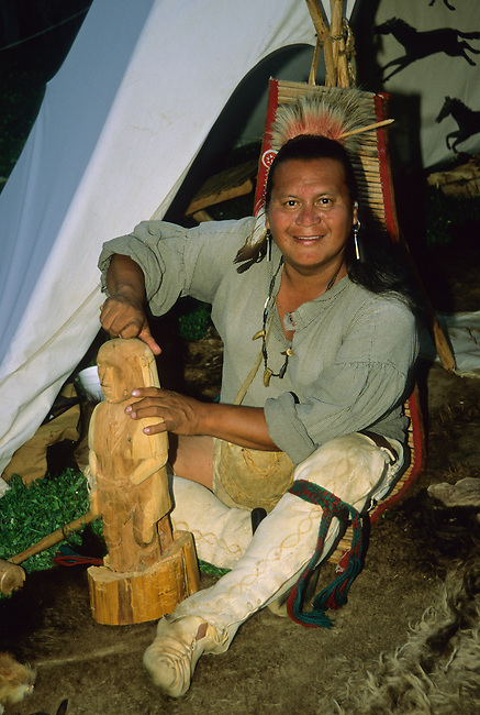 Cherokee man dressed in traditional regalia of the early 1800's demonstrates wood carving.