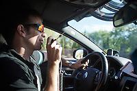 Team SKY DS Dario Cioni contacting fellow DS Gabriel Rasch over the radio<br /> <br /> stage 21: Alcala de Henares - Madrid (98km)<br /> 2015 Vuelta à Espana