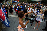 NEW YORK, NEW YORK - JULY 14: A woman shouts for a parlarte to ask for help from Cuban protesters in Union Square Park on July 14, 2021 in New York City. A small group of people gathered in Union Square Park in support of the Cuban people who have been protesting against the communist regime due to food shortages and the worsening of the economic crisis that has been exasperated by the coronavirus pandemic (COVID-19) . The protest on the island has been the largest protest against the government in decades. (Photo by Pablo Monsalve / VIEWpress via Getty Images)