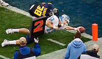 North Carolina quarterback T.J. Yates (13) dives into the endzone against West Virginia cornerback Keith Tandy (38) during the Meineke Car Care Bowl college football game at Bank of America Stadium in Charlotte, NC.
