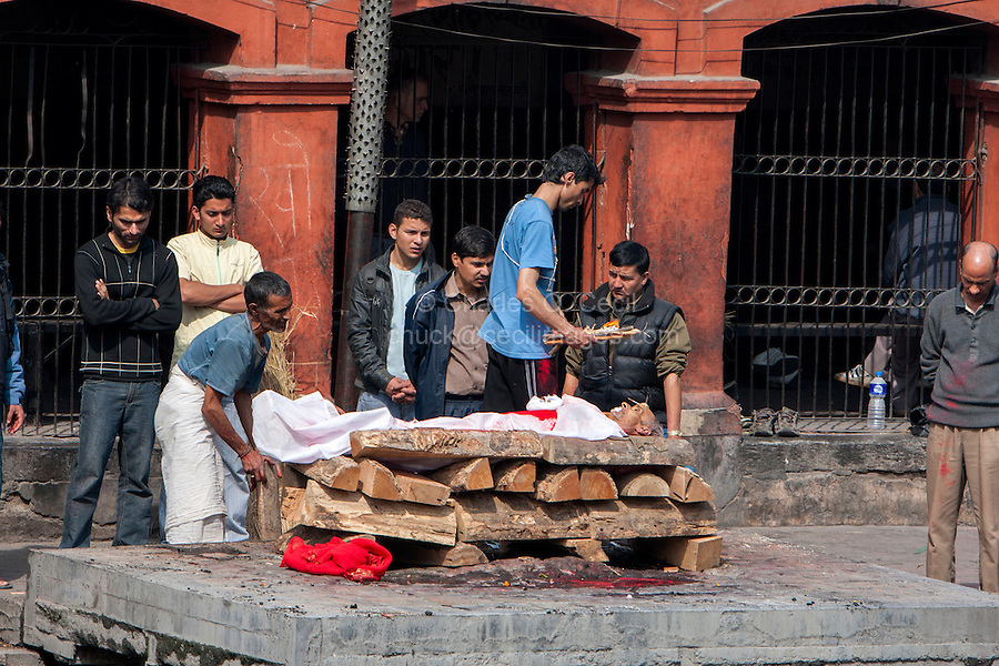 Nepal, Pashupatinath.  Cremation Stages.  With the body on the Cremation Site, Family Members Prepare to light the Fire.