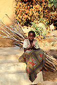 Kilamba, Tanzania. Girl sitting on steps with a bundle of firewood holding her hands in the traditional way.