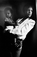 """USA. New York City. Spanish Harlem. Sala holds her younger brother Papo in her arms. The Puerto Rican family lives below the poverty line and receives public assistance (AFDC, Home Relief, Supplemental Security Income and Medicaid). The family resides in units managed by the New York City Housing Authority (NYCHA) which provides housing for low income residents. NYCHA administers rental apartments in facilities, popularly known as """"projects"""". Spanish Harlem, also known as El Barrio and East Harlem, is a low income neighborhood in Harlem area. Spanish Harlem is one of the largest predominantly Latino communities in New York City. 05.03.86 © 1986 Didier Ruef ."""