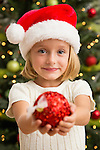Girl (6-7) in Santa hat holding Christmas bauble