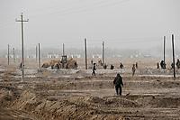 CHINA, autonomous province Xinjiang, uyghur worker prepare irrigation canals for a cotton plantation which belongs to a Han-chinese investor / CHINA, autonome Provinz Xinjiang, ausserhalb Kashgars, uigurische Arbeiter ziehen Bewaesserungsgraeben fuer eine Baumwollplantage am Rand der Taklamakan Wueste, die einem Han-chinesischen Investor gehoert, Hintergrund Bau von Haeusern fuer die Plantagenarbeiter