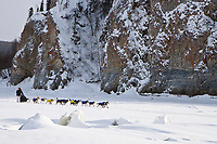 Hans Gatt on the Yukon River with cliffs in the background shortly after leaving the village checkpoint of Ruby in third place during the 2010 Iditarod