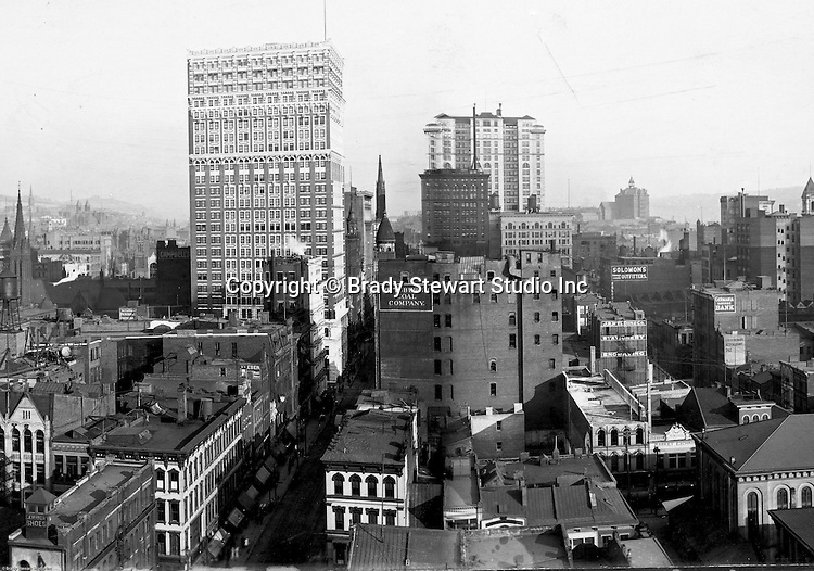 Pittsburgh PA:  View of City from the top of the Empire Building.  View of the city looking up Fifth Avenue.  <br /> <br /> Farmers Bank, Frick, and Arrott Buildings dominate the skyline.  Company signs on the city buildings include: C.A. Verner Shoes, George Reineman's Restaurant, Germania Savings Bank, Home Trust Company of Pittsburgh, JR Weldin & Company Stationery, Pittsburgh Coal, and Solomon's Outfitters