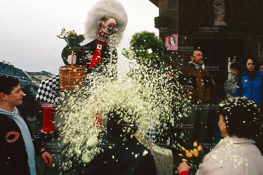 Switzerland. Basel. Fasnacht Carnival. On a bridge. A disguised person with white hair, a big nose, red socks, white gloves, yellow  flowers and pants with checked material throws confetti  on a woman. © 1997 Didier Ruef