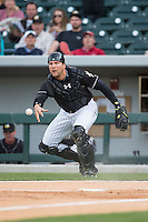 Charlotte Knights catcher Kevan Smith (32) flips the ball towards home plate during the game against the Toledo Mud Hens at BB&T BallPark on April 27, 2015 in Charlotte, North Carolina.  The Knights defeated the Mud Hens 7-6 in 10 innings.   (Brian Westerholt/Four Seam Images)