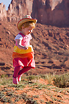 A young girl in a cowboy hat plays  in Monument Valley National Park.