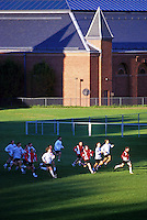 Overview of college soccer players running across an athletic field. Wesleyan University.