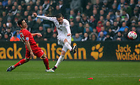 Gylfi Sigurdsson of Swansea City (R) takes a shot while being  challenged by Cameron Brannagan of Liverpool during the Barclays Premier League match between Swansea City and Liverpool at the Liberty Stadium, Swansea on Sunday May 1st 2016