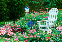 Adirondack chair in riotious garden with handpainted birdhouse