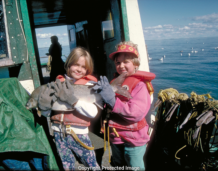 Two young girls hold a jumbo whitefish aboard a commercial fishing boat on Great Slave lake