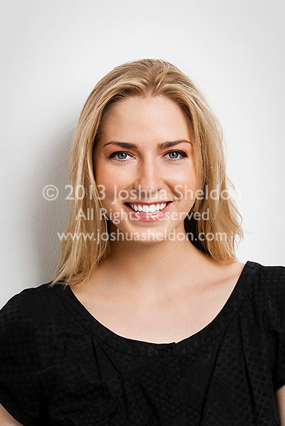 Young blonde woman looking at camera, smiling